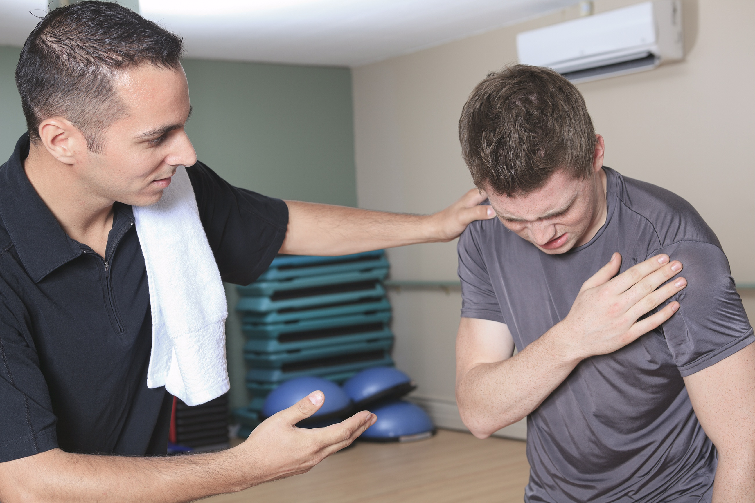 Athletic trainer helping athlete with shoulder pain
