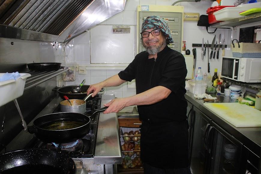 Marcos cocinando comidas tradicionales en la Brasería A Dos Ascuas, ubicado en calle Padre Alfonso Torres.