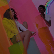 Two women smiling and hanging out in a colorful room