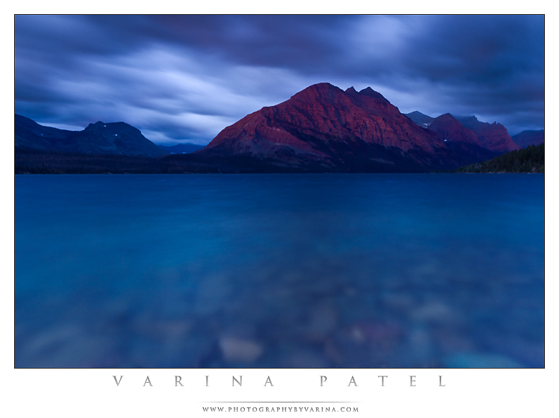 """Photo: Hold Your Breath  Get there early and use a long shutter speed to get images like this one from Glacier National Park in Montana.  Lots of you have been asking about my images from our recent trip to Glacier. I've been busy getting caught up, and writing up a lens review, and attending a multitude of soccer games... but I've have managed to find a few minutes to do some post-processing. So here it is. The first shot I've posted from beautiful, Glacier National Park.  We pay close attention to sunrise and sunset times when we are on location... but most of the time it's not so much about being there at the moment the sun peaks over the horizon. It's more about the light before and after that moment. We like to be there a good hour before sunrise - that gives us time to choose a composition, set up our camera gear, and do some low-light photography as the light begins to change.  The subtle magenta color you see on the mountain in this shot is called """"Alpenglow"""". It happens well before sunrise - this shot was taken nearly 20 minutes before the sun rose - and the colors started changing rapidly from that point on. The alpenglow faded as the sky began to glow in the East. By the time the sun appeared, the glow was long gone, replaced by rich golden light and a rainbow over the lake.  This was a tough shot to capture - more because of rain and splashing waves than particularly difficult camera settings. I wanted a 30 second shutter speed for a smooth opalescent effect... so I chose my settings accordingly. (f/8.0, 30 seconds, ISO 200.) Then, I wiped my lens clean and hoped for the best. I took three shots before the light faded - and only this one was was free of water droplets.  I've always loved long-exposure photography for the slightly surreal or dreamy effect it produces. What would you have done in a situation like this? Would you have been there in time to capture the glow? Or would you be kicking yourself later? :) I sure hope you wouldn't have missed it!"""