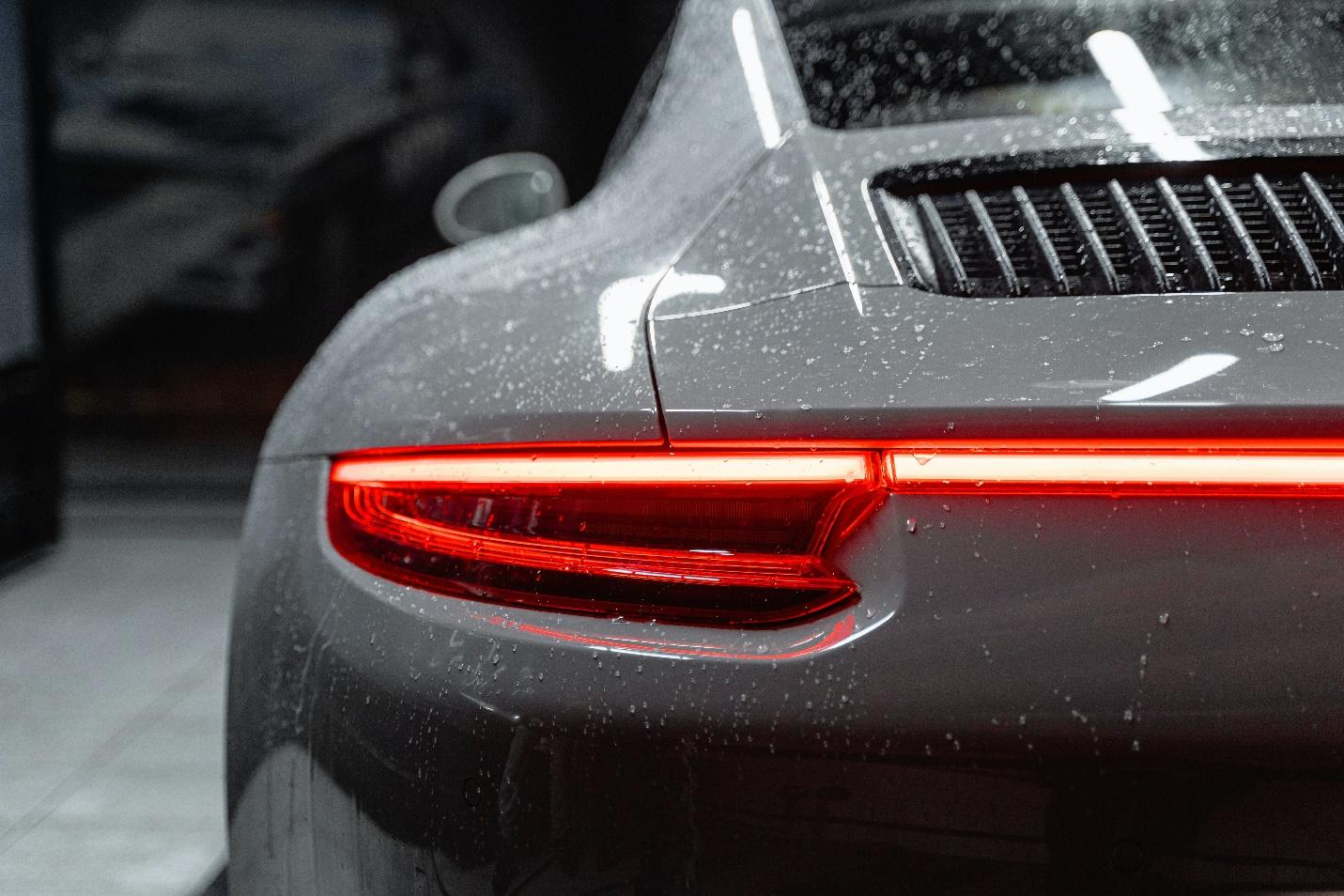 A Porsche with water droplets and its brake lights on. DIY car wash.
