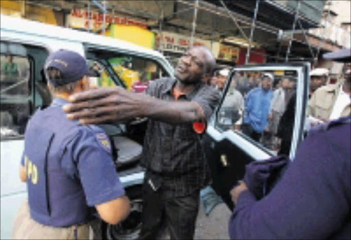 BLOCKADE: A taxi driver protests as metro police embark on Operation Nomakanjani at corner Plein and Wanderers streets in Johannesburg CBD. 16/03/09. Pic. Veli Nhlapo. © Sowetan.