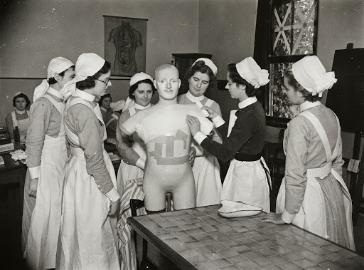 A sister tutor instructing student nurses bandaging a mannequin at Atkinson Morley's Convalescent Hospital, Copse Hill, Merton, Greater London