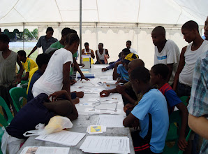 Photo: Youth at the SAREP table learning about the dangers of fecal contamination