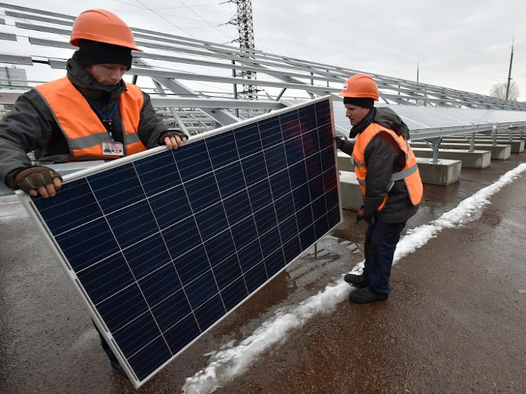 Workers install photovoltaic panels on the new one-megawatt power plant next to the New Safe Confinement over the fourth block of the Chernobyl nuclear plant on December 12, 2017.