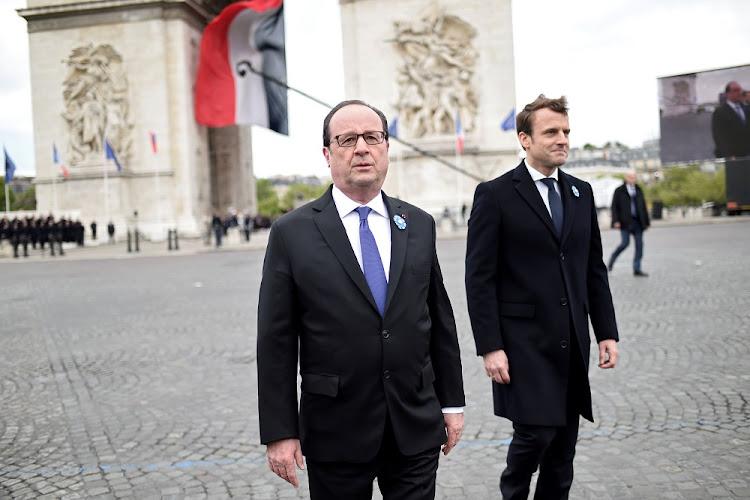 Outgoing French President Francois Hollande (left) and president-elect Emmanuel Macron attend a ceremony at  the Tomb of the Unknown Soldier at the Arc de Triomphe in Paris, France, on Monday. Picture: REUTERS