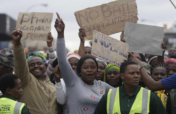 Protesters outside the Estcourt Magistrate's court on Monday, 8 August. Thursday's crowd gathered outside the court began shouting and hurling bins when they heard that charges had been withdrawn against two of the seven men accused of cannibalism.