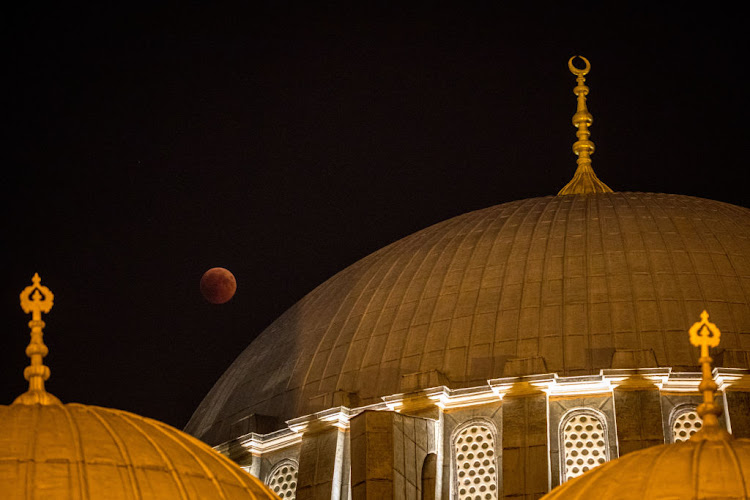 A total lunar eclipse is seen behind a dome of Istanbul's famous Suleymaniye Mosque on July 27 2018 in Istanbul, Turkey.