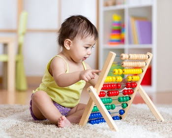 Toddler playing with abacus