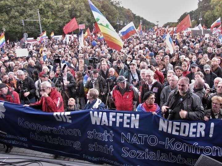 Massendemo mit Fahnen. Transparent: «Die Waffen nieder! Kooperation statt NATO-Konfrontation! Abrüstung statt Sozialabbau!».