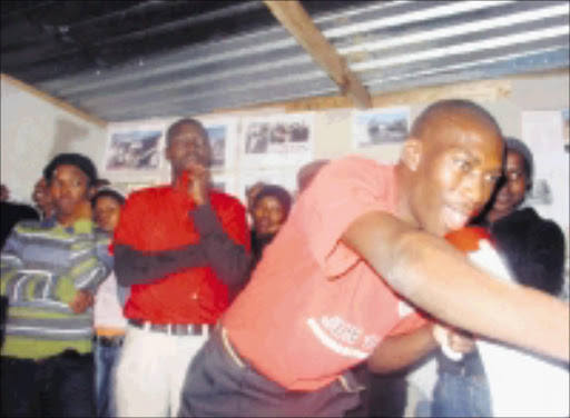 MAKING A POINT: QQ resident Mnikelo Ndabankulu speaks during a Khayelitsha shack dwellers meeting while Abahlali baseMjondolo Western Cape chairman Mzonke Poni looks on. Pic. Anna Majavu. 06/07/08. © Sowetan.