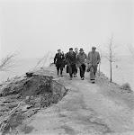 groep mannen lopen over smalle, deels afgekalfde, dijkweg. Aan beide zijden staat water