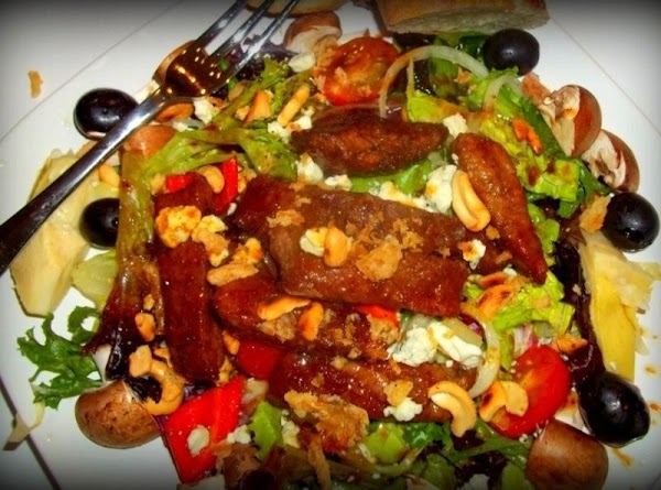 Now, divide the steak strips between the salads. sprinkle with cheese crumbles, cashews.  Now drizzle...