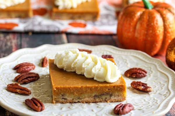 Tres Leches Pumpkin Pie Square With Whipped Topping Piped On Top.