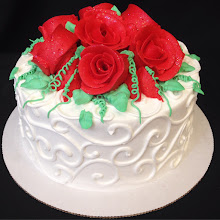Photo: Small wedding cake featufing Town&Country border in white w/ red frosting roses & green foliage.