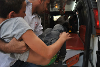 Photo: Another young boy is carried away into an ambulance.