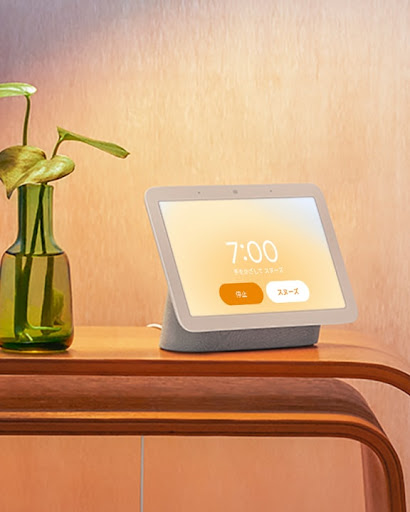 寝室のテーブルに置かれた Google Nest Hub。オレンジ色のバックライトが柔らかな画面に、いろいろな情報が表示されています。