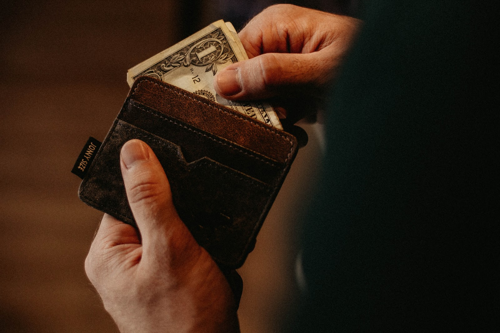 Person pulling money out of a wallet.