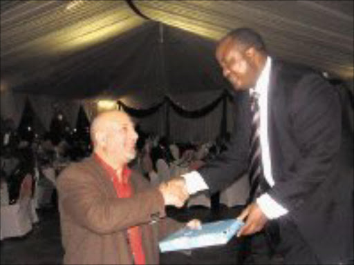 GREETINGS: Dr Hichem Benazzouz receives a gift from MEC for health William Lubisi. Pic. Riot Hlatshwayo. 07/05/08. © Sowetan.