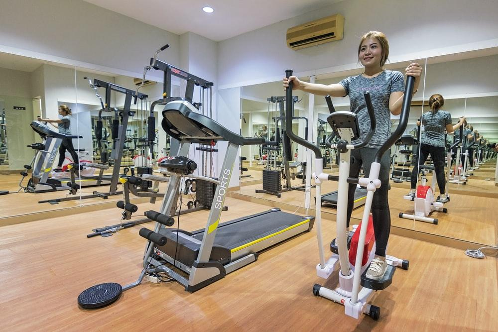 woman in gray long sleeve shirt standing on exercise equipment