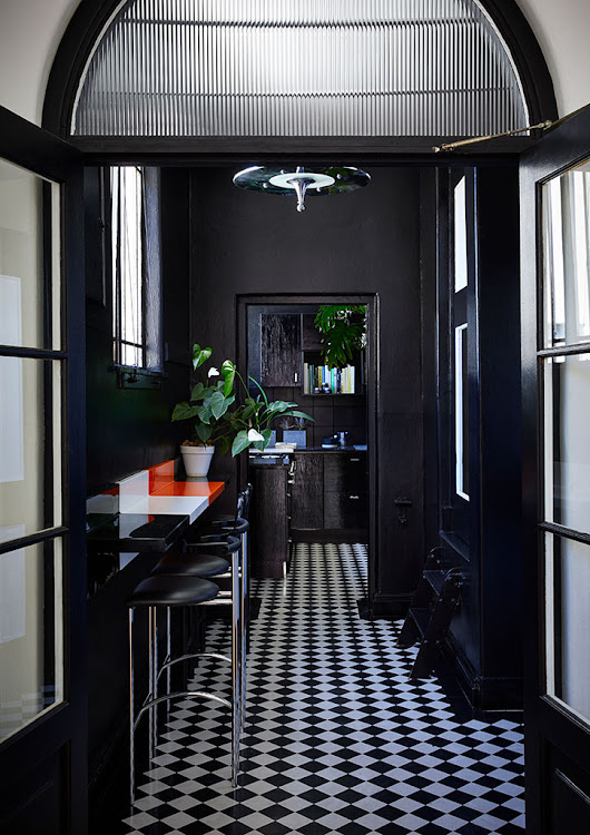 The kitchen features black-and-white checked linoleum floors.