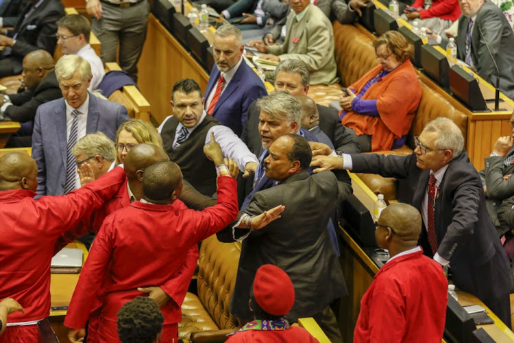 DA and EFF members confront each other during President Cyril Ramaphosa's question and answer session at the national assembly on November 6 2018 in Cape Town.