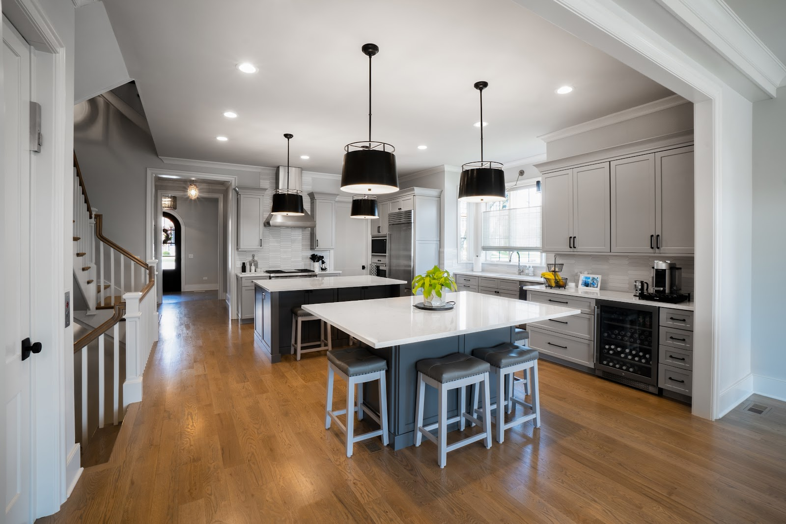 White Kitchen with dual contrasting colored eat-at islands, black drum pendant lighting with an open feel leading to the foyer and stairs.