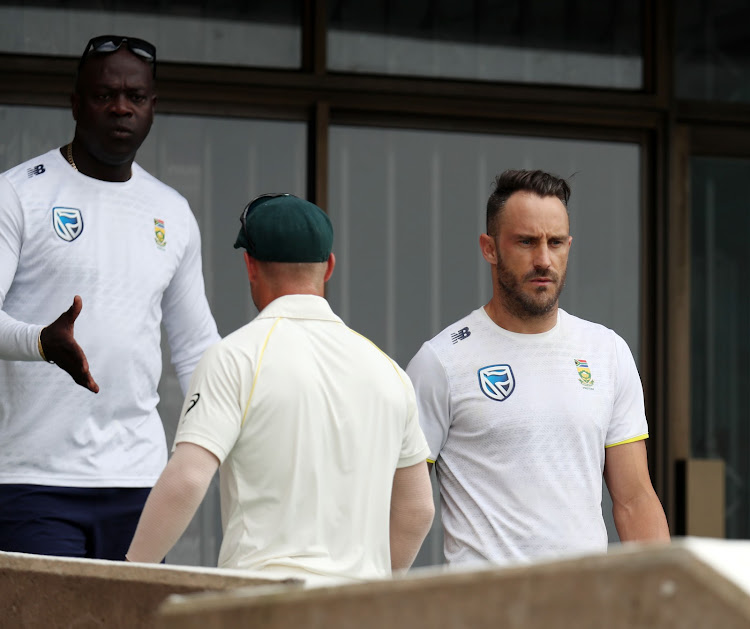 Head coach Ottis Gibson shakes the hand of Australia vice captain David Warner as Proteas captain Faf du Plessis looks on during the Sunfoil Test Series match between South Africa and Australia at Sahara Kings Park Stadium, Durban South Africa on the 05 March 2018.