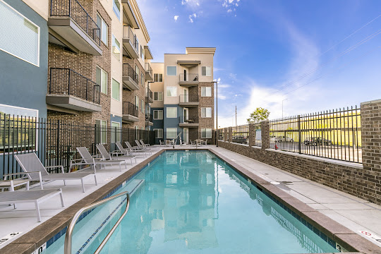 Pool photo with apartment building on left side and metal railing on right side