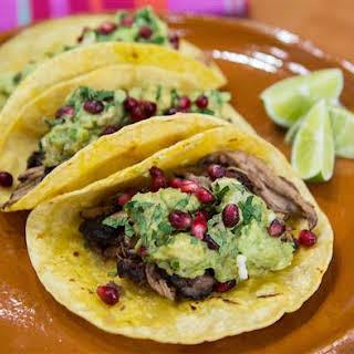 Pomegranate Pork Tacos with Guacamole and Queso Fresco.