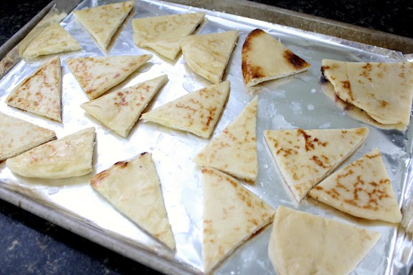 Naan cut into triangles on a sheet pan.