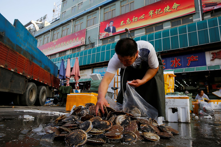 A retailer picks out clams from a pile at the seafood section of a fish market in Beijing.