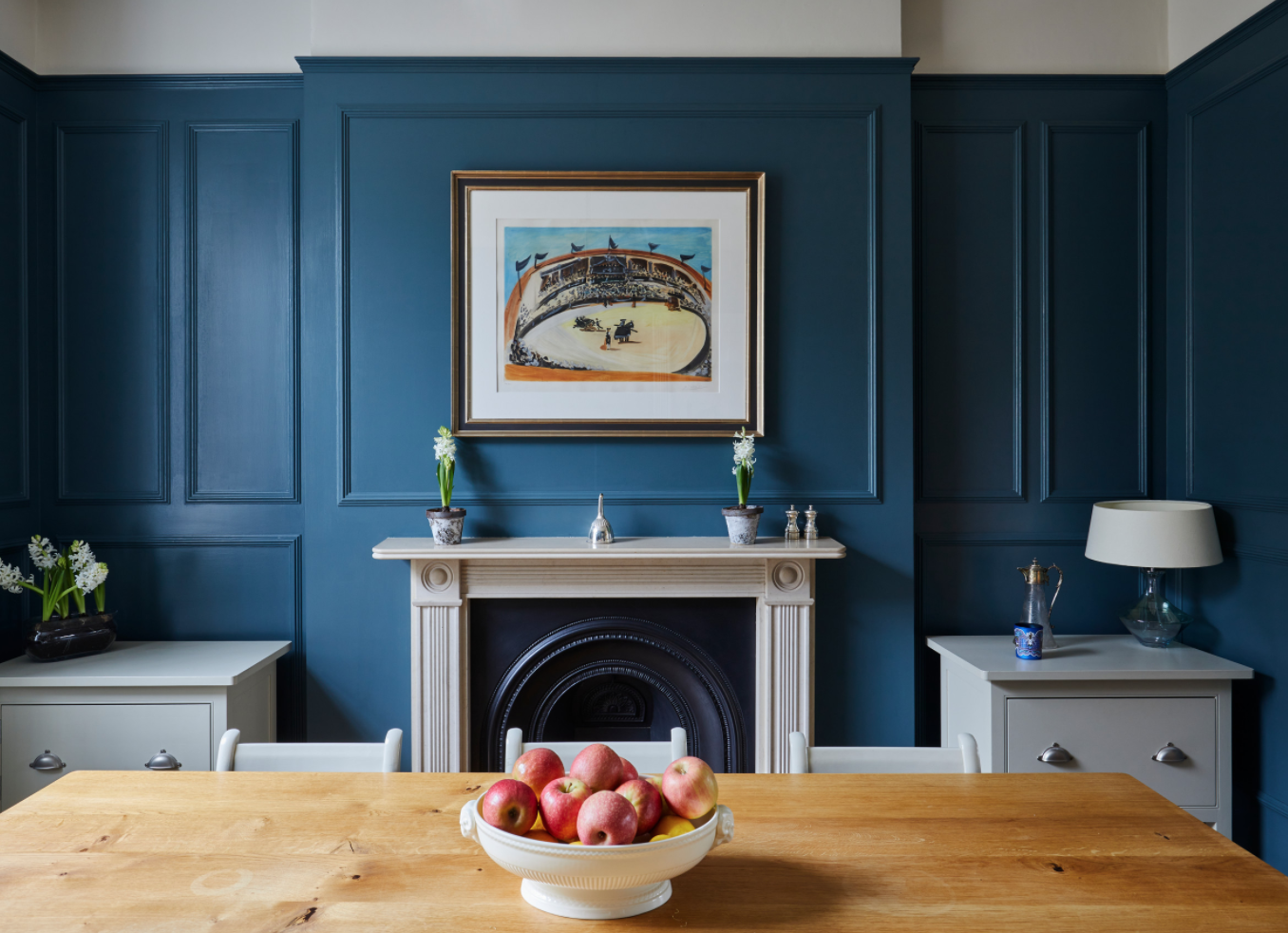 Dining room with dark blue panelled walls in a West London period home.