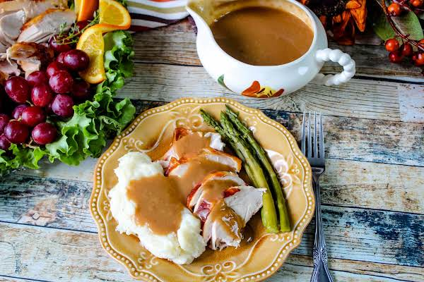 Turkey Gravy Poured Over Mashed Potatoes And Sliced Turkey.