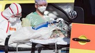 Un paciente con COVID-19, acompañado por sanitarios.