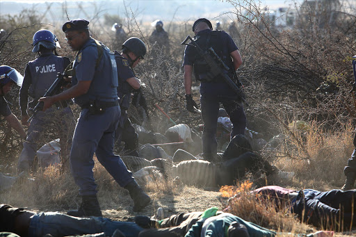 Police examine the scene in the aftermath of the Lonmin mine worker shooting at Marikana. File photo.