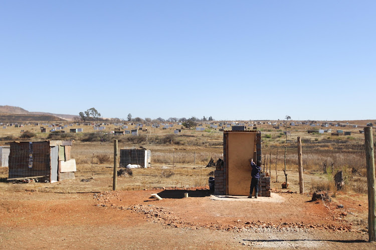A child makes his way to a newly-built toilet on Tuesday at Narens Farm near Lenasia South, Johannesburg. The area has recently seen mushrooming of new shacks.