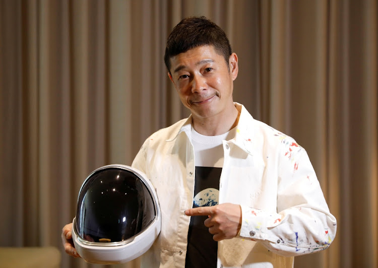 Japanese billionaire Yusaku Maezawa poses with a space suit helmet during an interview with Reuters in Tokyo, Japan on March 3 2021.