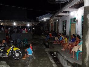 Photo: Village folks sitting on their home verandas to listen to the service.
