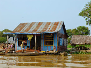Photo: This is a typical floating home with fishing nets being repaired and lotus growing out back.  When the rainy season comes, they move their home up the inlet, where our tour began.