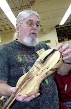 Photo: Ed Karch turned the body of the fiddle and hollowed through a hole in the bottom (he's pointing to it with his left index finger). He then added the top, fretboard, neck and other parts