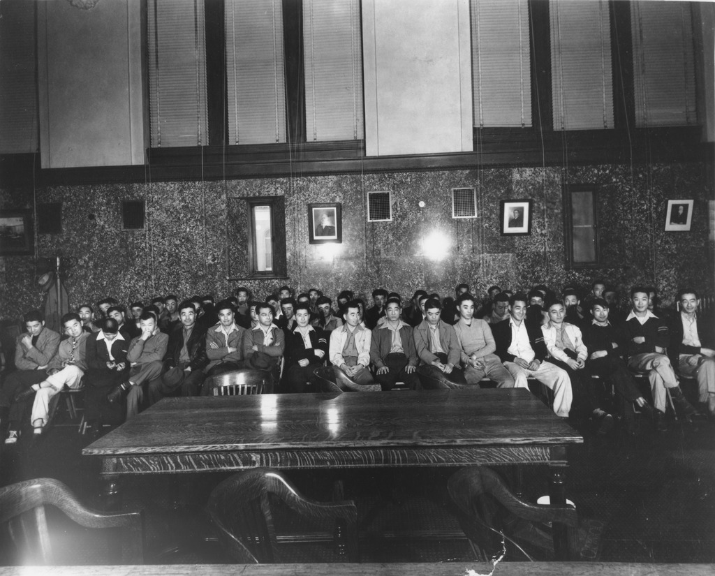 The 63 Heart Mountain draft resisters in a courtroom for the first day of their trial. The young men are seated in about three rows, with some standing against a wall in the back. Most are wearing sweaters and collared shirts, and some are smiling while others look more serious or pensive.