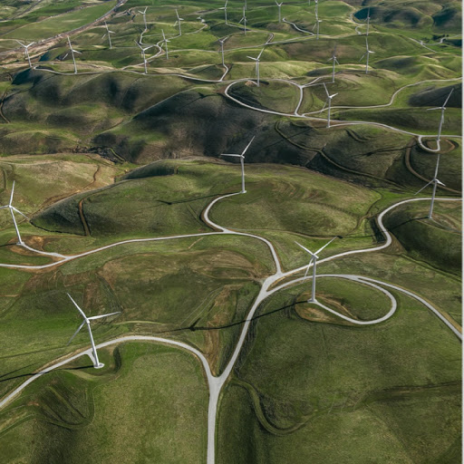 Ansicht von oben auf Windkraftanlagen in einer grünen Hügellandschaft