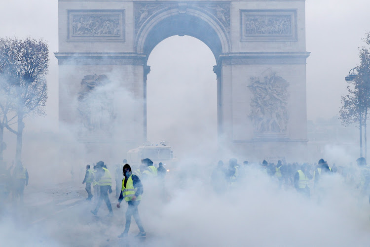 Protesters wearing yellow vests, a symbol of a French drivers' protest against higher diesel taxes, walk among tear gas during clashes with French riot police at the Place de l'Etoile near the Arc de Triomphe in Paris, France, December 1, 2018.