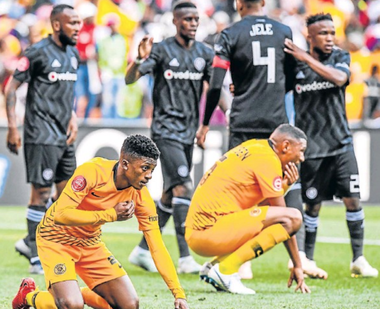 Orlando Pirates players celebrate in the background as Kaizer Chiefs players Dumisani Zuma, left, and Mario Booysen show their disappointment after their 2-1 defeat to Pirates in an Absa Premier League Soweto Derby fixture at the FNB Stadium on Saturday