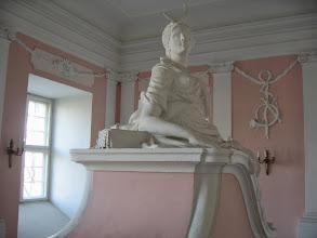 Photo: Posąg nocnej łowczyni Artemidy z kołczanem i sierpem księżyca nad czołem. W tle na ścianie róg myśliwski zawieszony na wstędze.