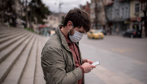 Man wearing mask on the street, shopping on his mobile device