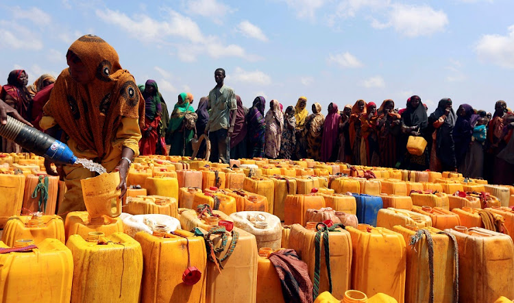 Internally displaced Somali women gather with their jerrycans to receive water at a distribution centre organized by a Qatar charity after fleeing from drought stricken regions in Baidoa, west of Somalia's capital Mogadishu, on Sunday. Picture: REUTERS/FEISAL OMAR