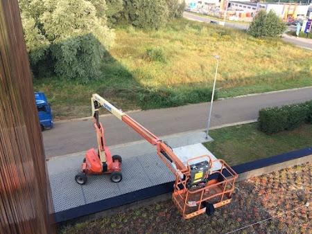 Olieën hout bedrijfsgebouw te Leuven - schilderen met hoogtewerker Leuven