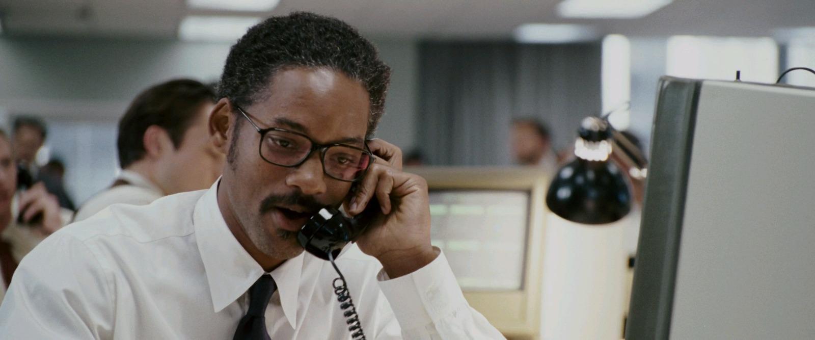 homem de camisa branca e gravata preta usando óculos falando ao telefone